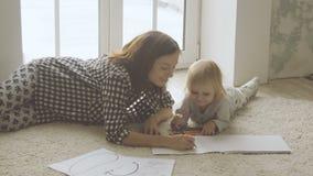La madre con la piccola figlia disegna con le matite in album stock footage