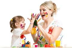 La madre con la pintura del niño y tiene pasatiempo de la diversión Foto de archivo libre de regalías