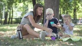La madre con los niños está bebiendo té en el parque almacen de video