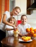 La madre con los niños exprimió el zumo de naranja Imagen de archivo libre de regalías