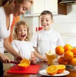 La madre con los niños exprimió el zumo de naranja Imágenes de archivo libres de regalías