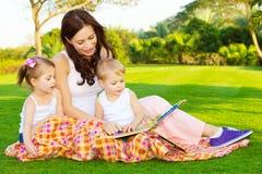 La madre con los niños leyó el libro Foto de archivo libre de regalías