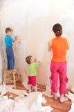 La madre con los niños quita los papeles pintados viejos Fotografía de archivo libre de regalías