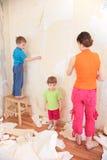 La madre con los niños quita los papeles pintados viejos de wa Foto de archivo