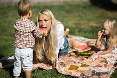 La madre con los niños se divierte en la hierba (en el jardín) Imagen de archivo libre de regalías