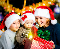 La madre con los niños abre la caja con los regalos de la Navidad Imagenes de archivo