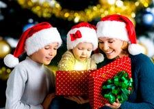 La madre con los niños abre la caja con los regalos en la Navidad h Fotos de archivo
