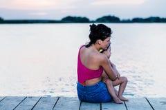 La madre con su hijo disfruta de la puesta del sol hermosa fotografía de archivo libre de regalías