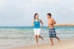 La madre con suo figlio sta correndo sulla spiaggia Fotografia Stock
