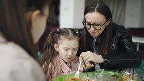 La madre con sus hijas almuerza en el caf? Hija de alimentaci?n de la madre qu? descontento de comer los tallarines almacen de metraje de vídeo