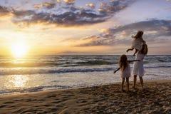 La madre con sus hijas disfruta de la puesta del sol foto de archivo