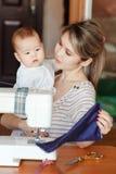 La madre con un bambino mostra il suo lavoro, cucente a casa Allevare i bambini, puericultura, babysitter Fotografia Stock