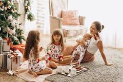 La madre con un bebé en sus manos sienta o la alfombra con sus dos hijas vestidas en pijamas que come las galletas con cacao fotografía de archivo