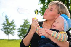 La madre con un niño infla burbujas de jabón Foto de archivo libre de regalías
