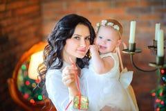 La madre con una piccola figlia nelle sue armi tiene un regalo fotografie stock libere da diritti