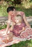 La madre con una sonrisa mira a la hija reflejada que lleva a cabo el appl Fotos de archivo libres de regalías