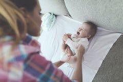 La madre cuidadosa pone los pañales al bebé gritador en el sofá foto de archivo