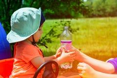 La madre dà alla neonata all'acqua della bevanda da un imbottigliare un parco Bevande di un anno del bambino ed esaminare una bot fotografia stock libera da diritti