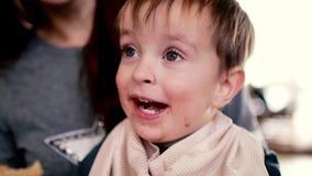 La madre dà gli alimenti per bambini da un bianco del movimento lento del cucchiaio del bambino archivi video