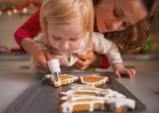 La madre d'aiuto del bambino decora i biscotti di natale con la glassa Immagine Stock