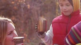 La madre da algo de té a los niños en parque del otoño metrajes