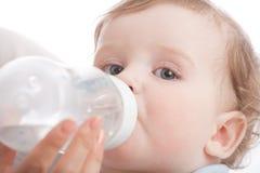 La madre da bebe a su hijo por la botella que introduce Imagen de archivo