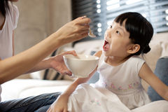 La madre da el alimento a su hija Imagen de archivo libre de regalías