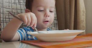 La madre da los alimentos para niños de una cuchara del bebé en un hogar, un niño come dispuesto 4K metrajes