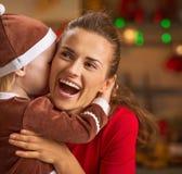 La madre de abarcamiento del bebé y en la Navidad adornó la cocina Fotografía de archivo libre de regalías