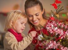 La madre de ayuda del bebé adorna el árbol de navidad Foto de archivo libre de regalías
