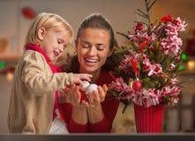La madre de ayuda del bebé feliz adorna el árbol de navidad Imágenes de archivo libres de regalías