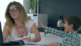 La madre de dos niños con los dolores de cabeza cansados, toma la cabeza en manos y la mirada en la cámara almacen de video