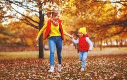 La madre de la familia y la hija felices del niño el otoño caminan Foto de archivo libre de regalías