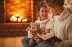 La madre de la familia y la hija felices del niño leyeron un libro en ev del invierno Imagen de archivo libre de regalías