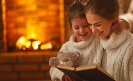 La madre de la familia y la hija felices del niño leyeron un libro en ev del invierno Foto de archivo