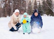 La madre de la familia y el bebé y el adolescente felices en invierno parquean Imagenes de archivo