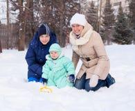 La madre de la familia y el bebé y el adolescente felices en invierno parquean Fotos de archivo libres de regalías