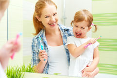 La madre de la familia y la muchacha felices del niño limpia los dientes con el cepillo de dientes Imágenes de archivo libres de regalías