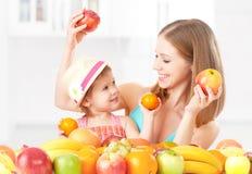 La madre de la familia y la niña felices de la hija, comen la comida vegetariana sana, fruta Fotos de archivo libres de regalías