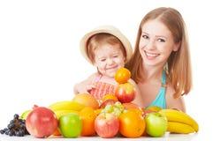 La madre de la familia y la niña felices de la hija, comen la comida vegetariana sana, fruta aislada Fotos de archivo