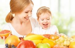 La madre de la familia y la niña felices de la hija, comen vegeta sano Imágenes de archivo libres de regalías