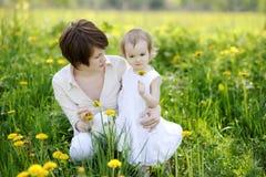 La madre de Youn y su muchacha en dientes de león colocan Fotografía de archivo libre de regalías