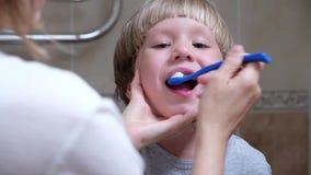 La madre del primer ayuda a limpiar los dientes a su pequeño hijo por la mañana Hijo de ayuda de la mujer cepillar sus dientes almacen de video