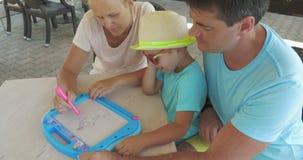 La madre del reloj del padre y del hijo está pintando el animal doméstico en tablero del imán almacen de video