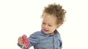 La madre del ` s del niño pequeño le da un caramelo sabroso Fondo blanco Cámara lenta almacen de video