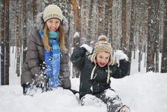 La madre dell'inverno con suo figlio concede la seduta sulla neve nel wo Immagini Stock Libere da Diritti