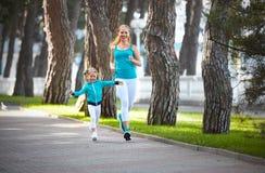 La madre della famiglia di sport e la figlia del bambino sono impegnate nel manteneree la a immagine stock