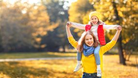 La madre della famiglia e la figlia felici del bambino sull'autunno camminano Immagine Stock