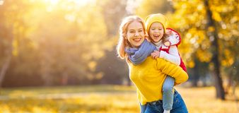 La madre della famiglia e la figlia felici del bambino sull'autunno camminano