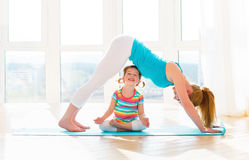 La madre della famiglia e la figlia del bambino sono impegnate nella forma fisica, yoga a Fotografie Stock Libere da Diritti
